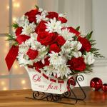 Reference  16-C4 Starting at 49.95 Ride into the season with a joyful burst of holiday blooms! A modern, fresh take on the traditional sleigh arrangement, we bring together red roses, red carnations, and red mini carnations, offset by snowy white Peruvian lilies and chrysanthemums.