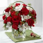 Reference # B14-4965 Starting at $54.99 ich red roses and mini carnations are beautifully accented with white Peruvian lilies, red hypericum berries, lily grass blades, and an assortment of lush holiday greens to create an exceptional fresh flower arrangement. Presented in a clear glass cube, this h