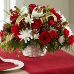 Reference # B17-5134 Starting at $49.99  Rich red roses, red mini carnations, white chrysanthemums, red hypericum berries, and fresh Christmas greens are accented with natural pine cones and a stylish red, green, and white striped grosgrain ribbon while situated in a round white wash woven handled b