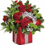 Reference # T16 Starting at $54.99 his will surely be a holiday décor favorite for years to come! This festive mix features red roses, red miniature carnations, green button spray chrysanthemums, flat cedar, variegated holly and noble fir. Delivered in Teleflora's Gift Wrapped ornament keepsake box.