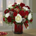 "Reference # 16-C6 Starting at $ 49.99 Composed of white roses (in Deluxe, Premium and Exquisite versions only) and cushion pompons, burgundy carnations, Christmas greens with holly berries and ""frosted"" pinecones, this arrangement is accented with bright tartan bows in a ruby-hued glass ""lantern"" va"