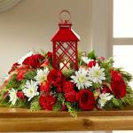 Reference #16-C3  Starting at $ 69.99 Red roses, carnations, and mini carnations are beautifully arranged amongst white chrysanthemums, and an assortment of holiday greens all surrounding an attractive red lantern with a lattice pattern housing a single white votive candle. A great gift for friends