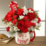 "Reference #16-C7 Starting at $49.99  We bring together red roses, carnations, and mini carnations mingling with snowy white Peruvian lilies and an assortment of Christmas greens, arranged to perfection in a keepsake ceramic Santa mug with the word, ""Believe,"" at the bottom in a lively font. P"