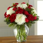 Reference #16-C7 Starting at  $59.99 Gorgeous and full white snowball chrysanthemums are not to be upstaged when arranged amongst rich red roses, red carnations, and red mini carnations, accented with red hypericum berries and assorted Christmas greens to create a standout yuletide display