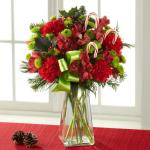 Reference # B13-5130 Starting at 45.99 Frilly red carnations are paired with red Peruvian Lilies surrounded by green button poms, variegated holly, and an assortment of fragrant Christmas greens. Accented with a bright green satin ribbon and classic candy canes.