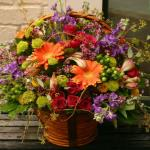 Reference JBS  0110 Starting at $ 69.99  Full lush basket of assorted mums, roses, alstromeria, gerbera daisies and seeded eucalyptus arrangement in a brown handled basket. Upgrades include additional roses and larger baskets.