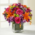 Reference # D2-5189 Starting at  $   49.99                        Hot pink roses and orange Asiatic Lilies  vibrant by purple Peruvian Lilies, hot pink mini carnations, green button poms, purple statice & an assortment of lush greens. Accented with assorted curling ribbons .