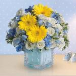 Reference #  T34-2B Starting at $44.95 The glass block will make an adorable display piece for years!<br/><br/>Dazzling white spray roses, light blue delphinium, white waxflower and light blue organza ribbon are delivered in a clear baby block with a light blue liner.