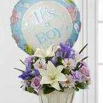 "Reference # D7-4903 Starting at  $54.95 Lavender roses, blue iris, lavender carnations, lavender daisies, white Asiatic lilies and lush greens are beautifully arranged in a round whitewash basket. Presented with a Mylar balloon declaring, ""It's A Boy!""."