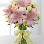 Reference #  D7-4906d Starting at $39.99 Pink roses, pink Asiatic lilies, pale peach carnations, pale green mini carnations and lush greens are exquisitely arranged in a clear glass gathered square vase. Accented with a pink satin ribbon, this flower bouquet creates beautiful  gift.