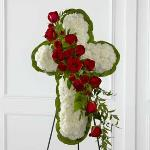 Reference # S12-4464 Standing Cross White carnations are arranged to form a cross in which an accent of red roses, spray roses, and lush greens are draped across the center,